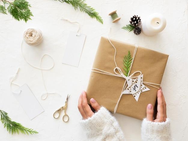 Рождественский подарок концепции. самодельная упаковка рождественских подарков крафтовой бумагой, инструментами и украшениями. вид сверху Premium Фотографии