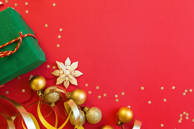 Christmas gift, golden toys lying on red background with confetti Premium Photo