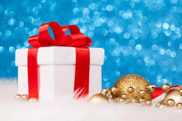Рождественский подарок с украшением на синей блестящей поверхности Premium Фотографии