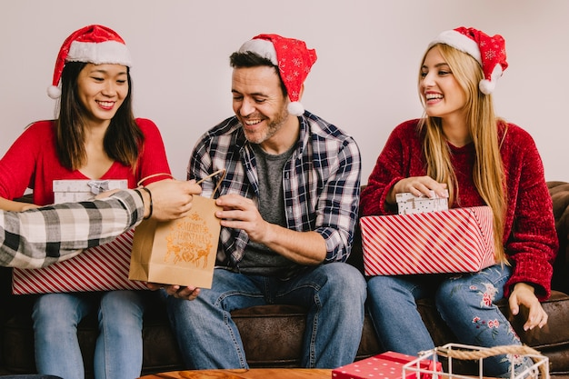 Christmas gifting concept with three friends Free Photo