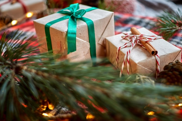 Christmas gifts on the background of a red woolen checkered plaid with garlands of cones and fir branches Premium Photo