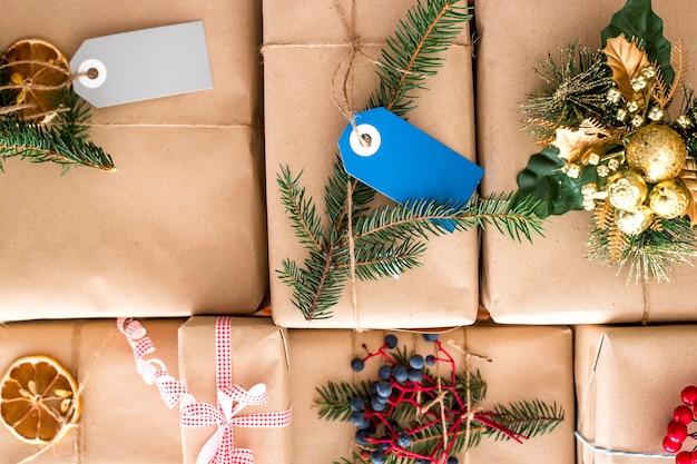 전나무 가지로 장식 된 공예 종이로 포장 된 크리스마스 선물 프리미엄 사진