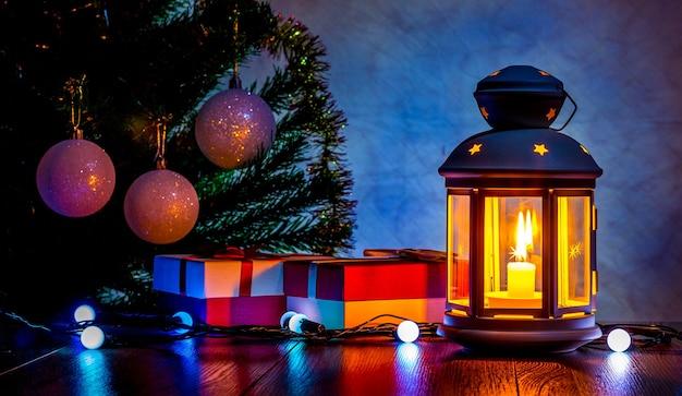 キャンドルとランタンの光の中でクリスマスツリーの下のクリスマスプレゼント Premium写真