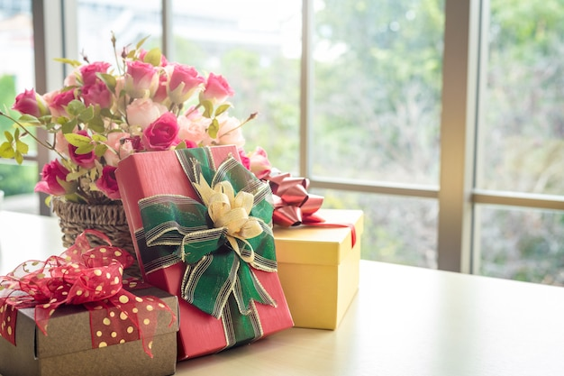 Christmas gifts with rose vase and santa hat on wooden table interior of room view through window Premium Photo