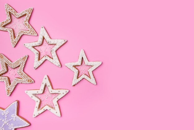 Рождественские пряники звезды на сладком розовом фоне. вид сверху. Premium Фотографии