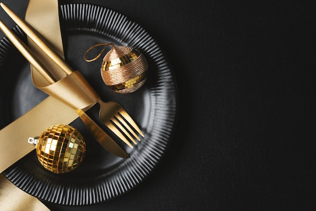 Christmas golden cutlery on plate with bauble and ribbon on dark background. Premium Photo