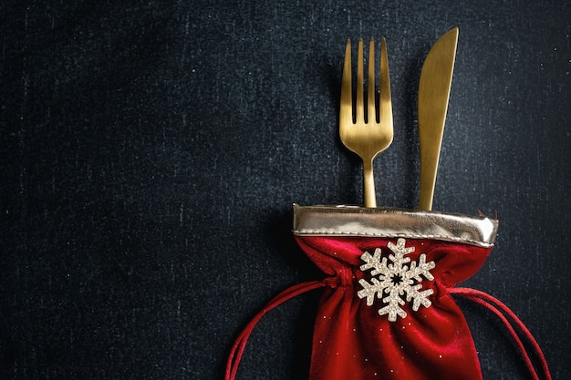 Christmas golden cutlery in small textile bag with snowflake and ribbon on dark background. Premium Photo