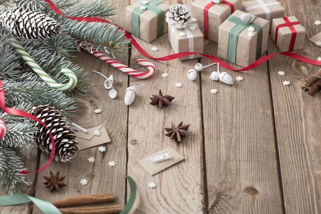 Рождественская зеленая ветвь и подарки на деревянном фоне Premium Фотографии
