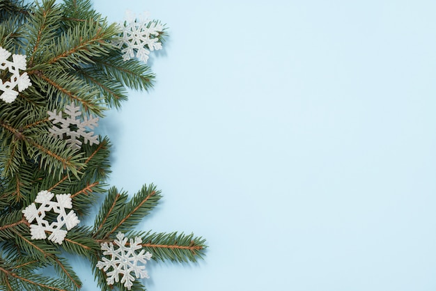 Christmas . green tree and snowflakes decorations on blue background. top view with copycopyspace. Premium Photo