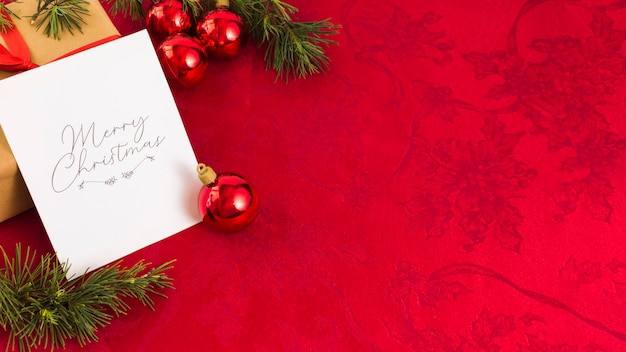 Christmas greeting card with red baubles Free Photo