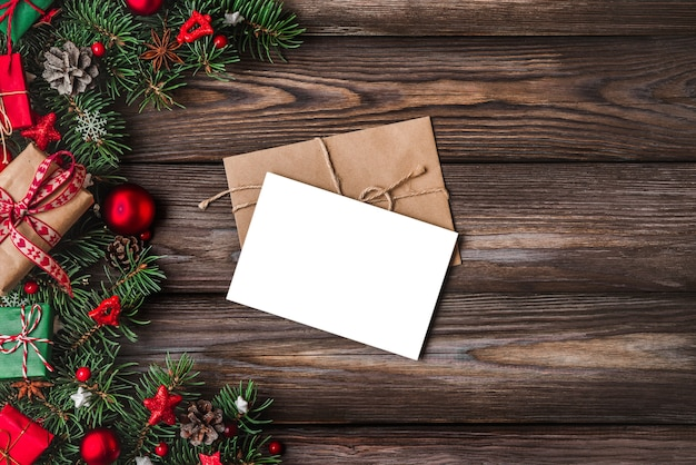 Christmas and happy new year greeting card with fir tree branches, gift boxes, decorations Premium Photo