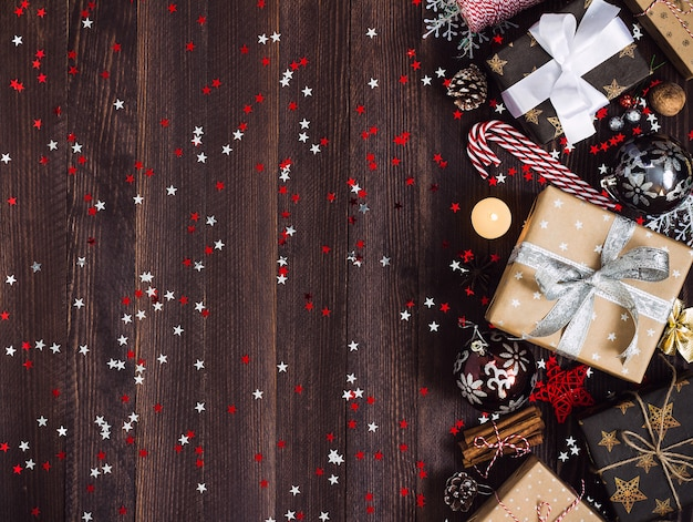 Christmas holiday gift box on decorated festive table with pine cones candy cane candle ball Free Photo
