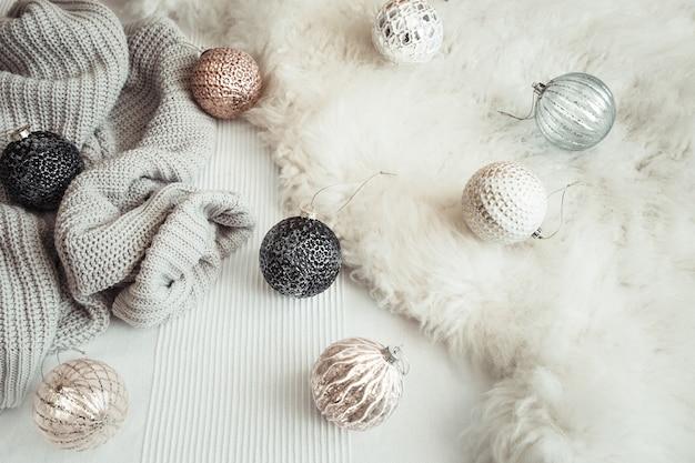 Рождественский праздничный натюрморт с декоративными игрушками и вязанным свитером. Бесплатные Фотографии