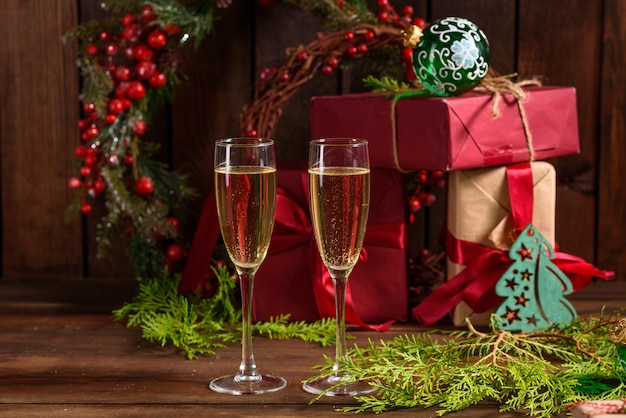 Christmas holiday table with glasses and a bottle and gifts Premium Photo