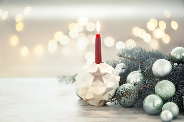 Christmas holiday wall with a candle in a candlestick. Free Photo