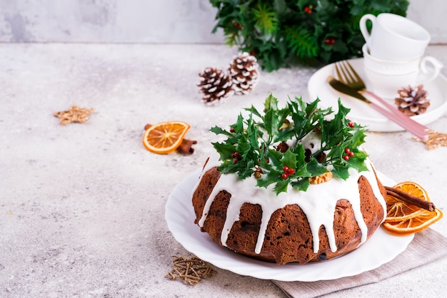 Christmas homebaked dark chocolate bundt cake decorated with white icing and holly berry branches close-up Premium Photo