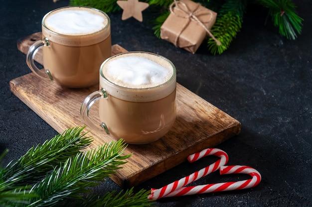 クリスマスのホットドリンク。キャンディー、ギフトボックス、枝モミの木と暗いテーブルの上のグラスにココアコーヒーまたはチョコレート。 Premium写真