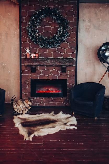 Interno di natale decorato con ghirlanda di natale fatta di rami di abete. due poltrone e una vera pelliccia di animali sul pavimento davanti a un camino elettrico. Foto Gratuite