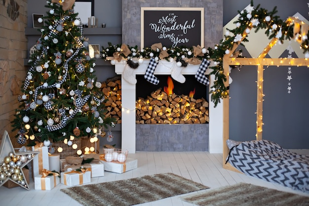 Christmas interior of living room with decorated christmas tree,  fireplace with christmas socks and wooden bed in shape of house. stylish interior of children's room, room decor in rustic style  loft Premium Photo