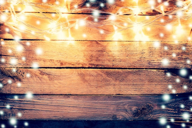 Christmas Light And Snow On Wooden Background With Space Photo