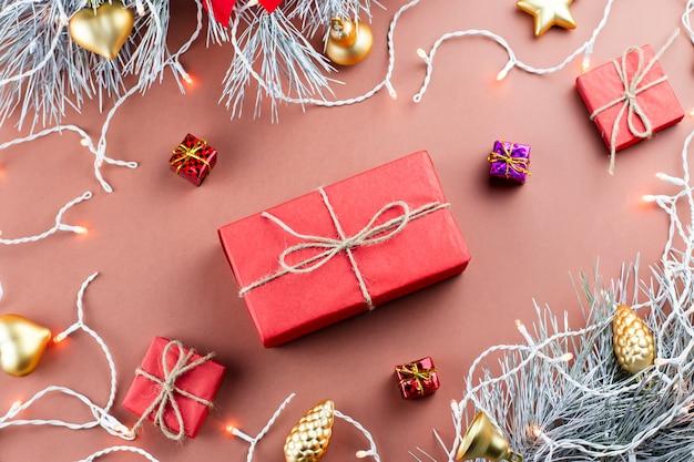 Рождественские огни, подарочная коробка, подарки, золотые украшения и еловые ветки на коричневом фоне Premium Фотографии
