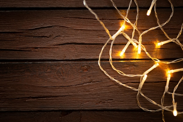 Christmas lights on a old textured wooden background Free Photo