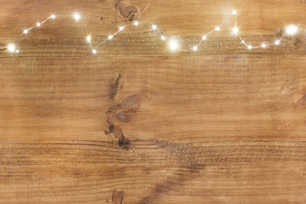 Christmas lights on top on wooden background. Free Photo