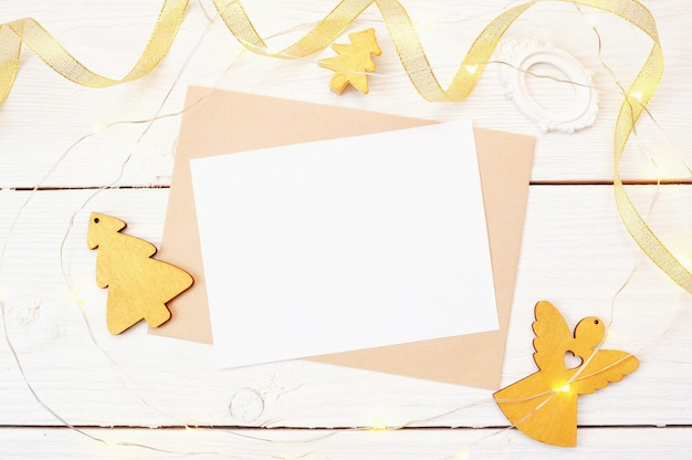 Christmas mail on a white wooden background with a golden angel and christmas tree. flat lay top view photo mockup. Premium Photo
