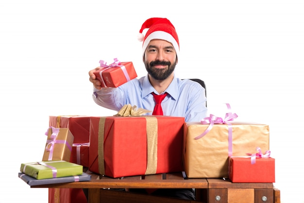 Christmas man in his office with several gifts Photo | Free Download