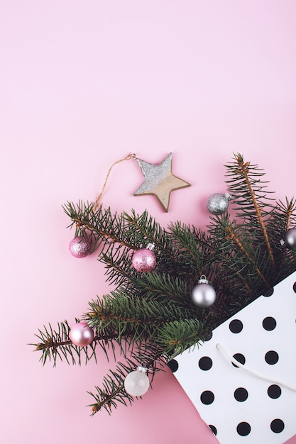 Christmas minimal flat lay composition with fir branches, shiny christmas balls, wooden star in polka dot gift bag Premium Photo