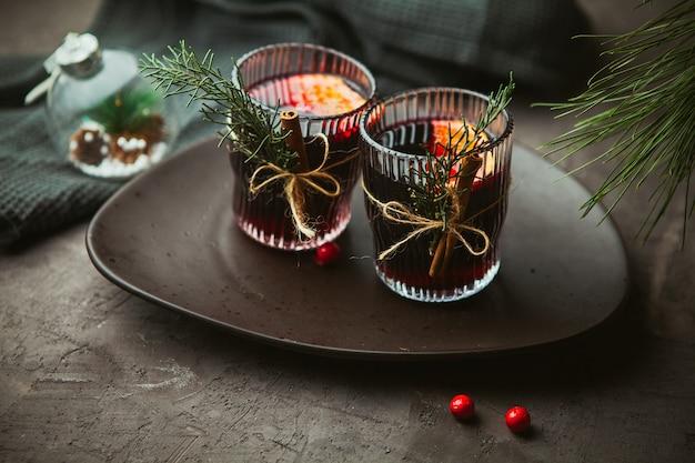 クリスマスは、プレートに香辛料と柑橘系の果物を添えた赤ワインをクローズアップで混ぜ合わせました。クリスマスの時期の伝統的な温かい飲み物 Premium写真