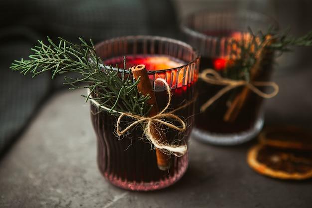 クリスマスは、黒い表面に芳香のあるスパイスと柑橘系の果物を使った赤ワインを混ぜ合わせました。クローズアップ。クリスマスの時期の伝統的な温かい飲み物 Premium写真