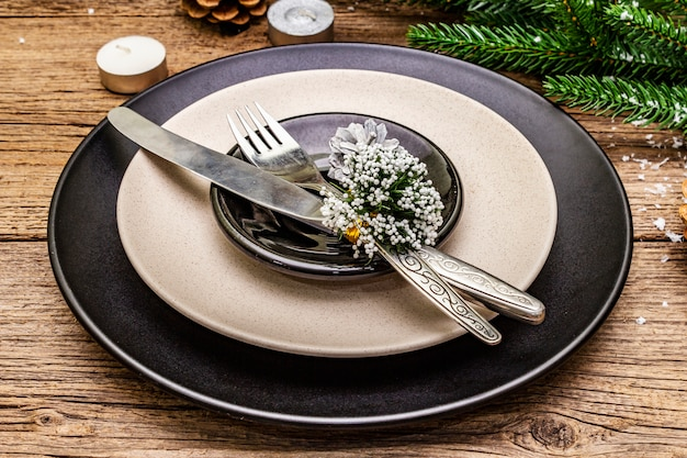 Christmas and new year dinner place setting. evergreen fir tree branch, candles, cones, ceramic plates, fork and knife. Premium Photo