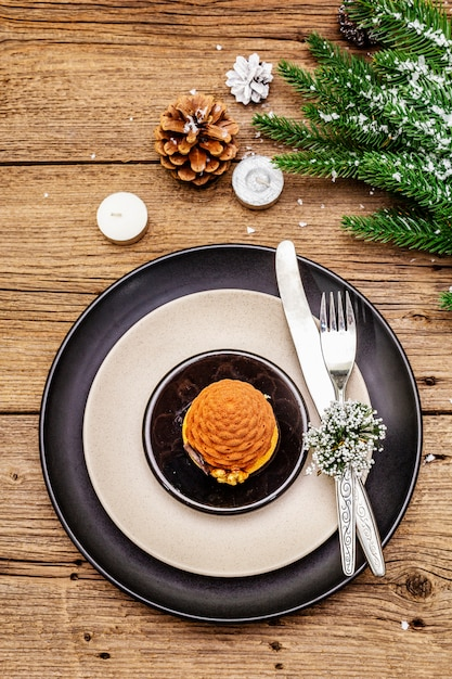 Christmas and new year dinner place setting. sweet snack, fir tree branch, candles, cones, ceramic plates, fork and knife. Premium Photo