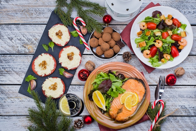Christmas or new year family dinner setting table concept with holiday decoration. delicious roast steak salmon, salad, appetizers and dessert on white wooden . top view Premium Photo