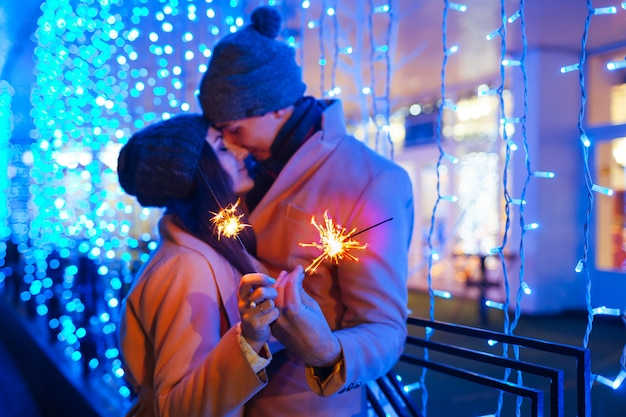 Christmas and new year fun concept. couple in love burning sparklers by holiday illumination outdoors. festive holidays Premium Photo