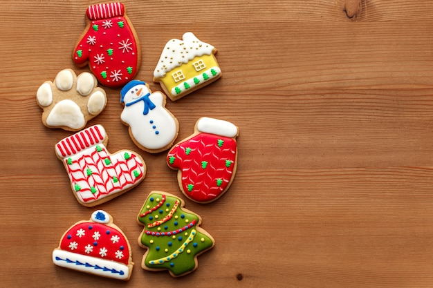 Christmas new year holiday background, colorfull gingerbread cookies and cones on wooden table. copy space. holiday concept. Premium Photo