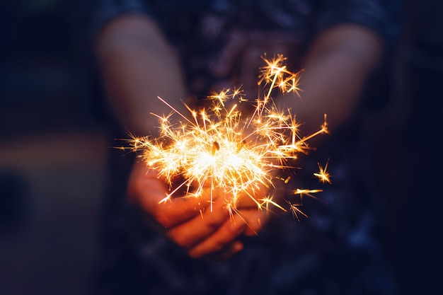 Christmas, new year sparkler in woman hands. Premium Photo
