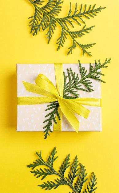 Рождество, новый год, день святого валентина желтый фон с подарочной коробкой diy, украшенной желтой лентой с бантом и зелеными ветвями туи на ярко-желтом фоне. вид сверху. вертикальная ориентация. Premium Фотографии