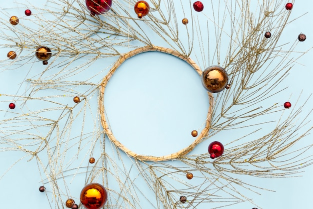 Christmas or new year winter composition. round frame made of golden tree branches and decorative christmas ornaments. Premium Photo