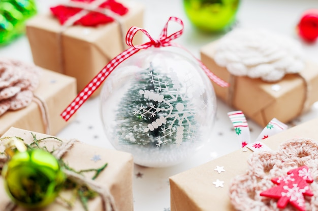 Christmas and new year with presents, decorations and transparent decorative ball with fir tree inside. Premium Photo