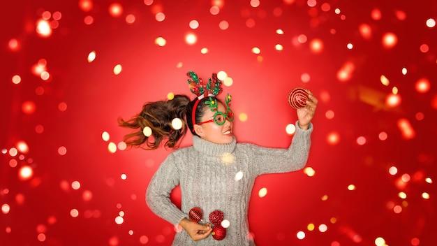 크리스마스 새해. 젊은 여자 손질 빨간 벽에 휴일에 크리스마스 장식품과 소품 공 빨간색 따뜻한 스웨터를 입고. 개념 메리 크리스마스. 프리미엄 사진