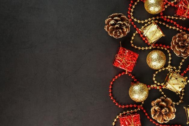 Рождество или новый год темный фон с красными и золотыми украшениями для елки со свободным пространством. вид сверху. рождественское настроение. Premium Фотографии
