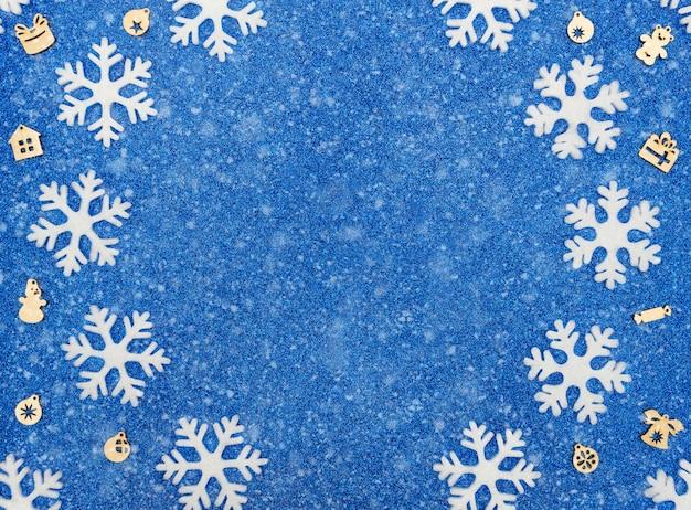하얀 눈송이, 크리스마스 나무 장식과 눈 크리스마스 또는 겨울 파란색 배경. 복사 공간이있는 평면 위치 스타일. 프리미엄 사진