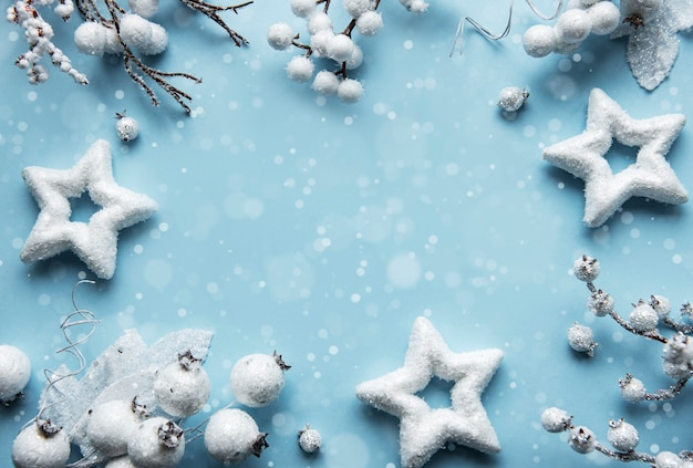 パステルブルーの背景に白い装飾で作られたクリスマスまたは冬の構成フレーム Premium写真
