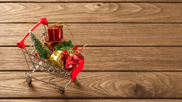 Christmas ornaments on miniature shopping cart over the wood for web banner Premium Photo
