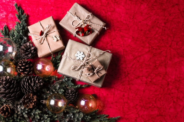 Christmas ornaments on red background with wrapped gifts Free Photo