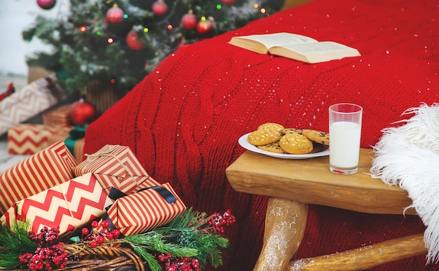 Christmas photo book with cookies and a glass of milk on the bed. selective focus. Premium Photo