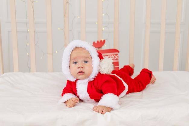 Новогоднее фото младенца в костюме санты, лежащего в кроватке дома Premium Фотографии