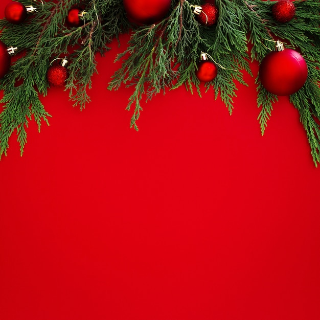 Christmas pine leaves decorated with red balls on red background with copyspace Free Photo